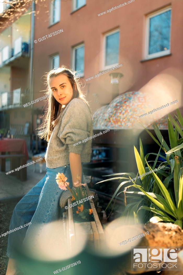 Stock Photo: Portrait of young woman in garden in sunshine.
