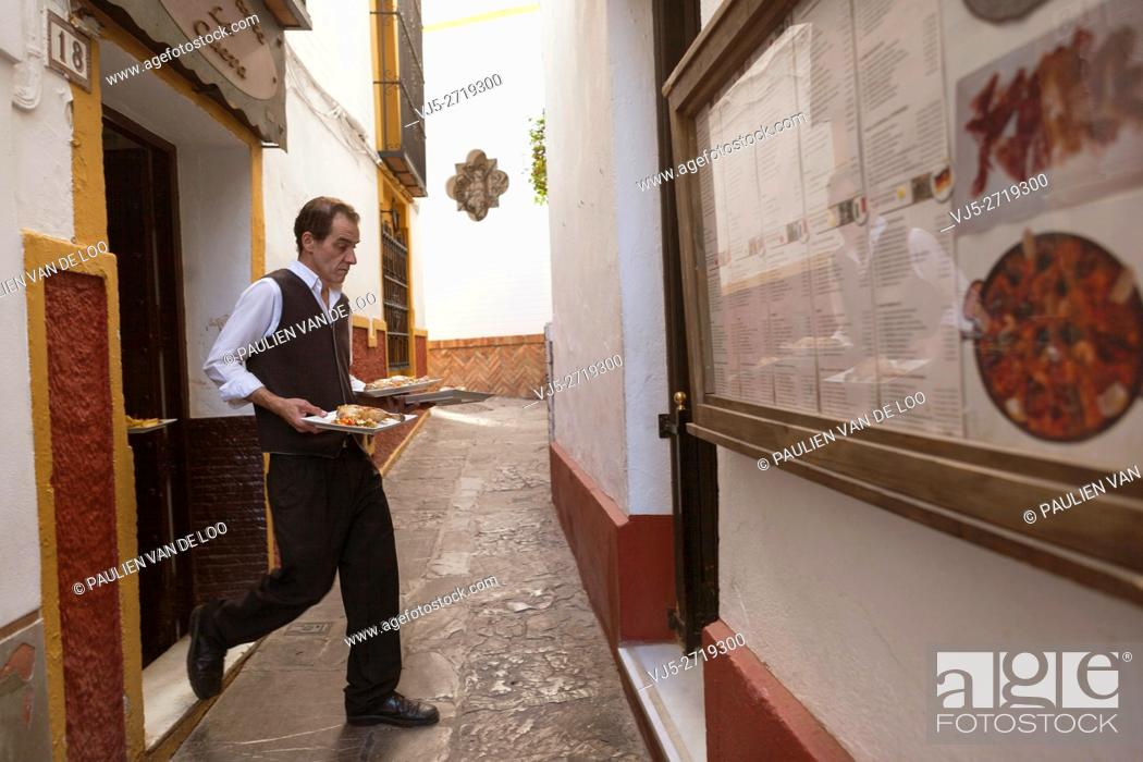 Stock Photo: Sevilla, Spain, a waiter rushes from the kitchen to the other location to serve customers wih food.
