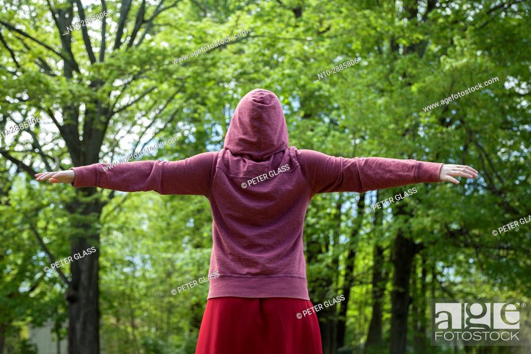 Stock Photo: Young woman, arms extended, her back to the camera, wearing a red sweatshirt and hoodie, and standing in front of trees in a park.