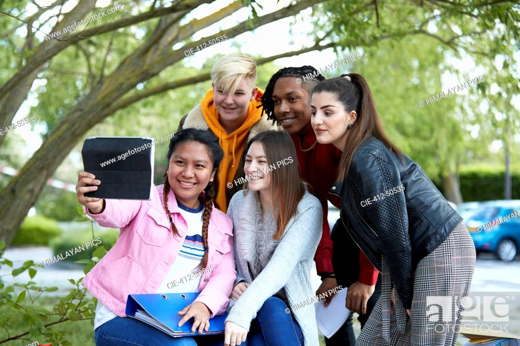 Stock Photo: Happy college students taking selfie with digital tablet in park.