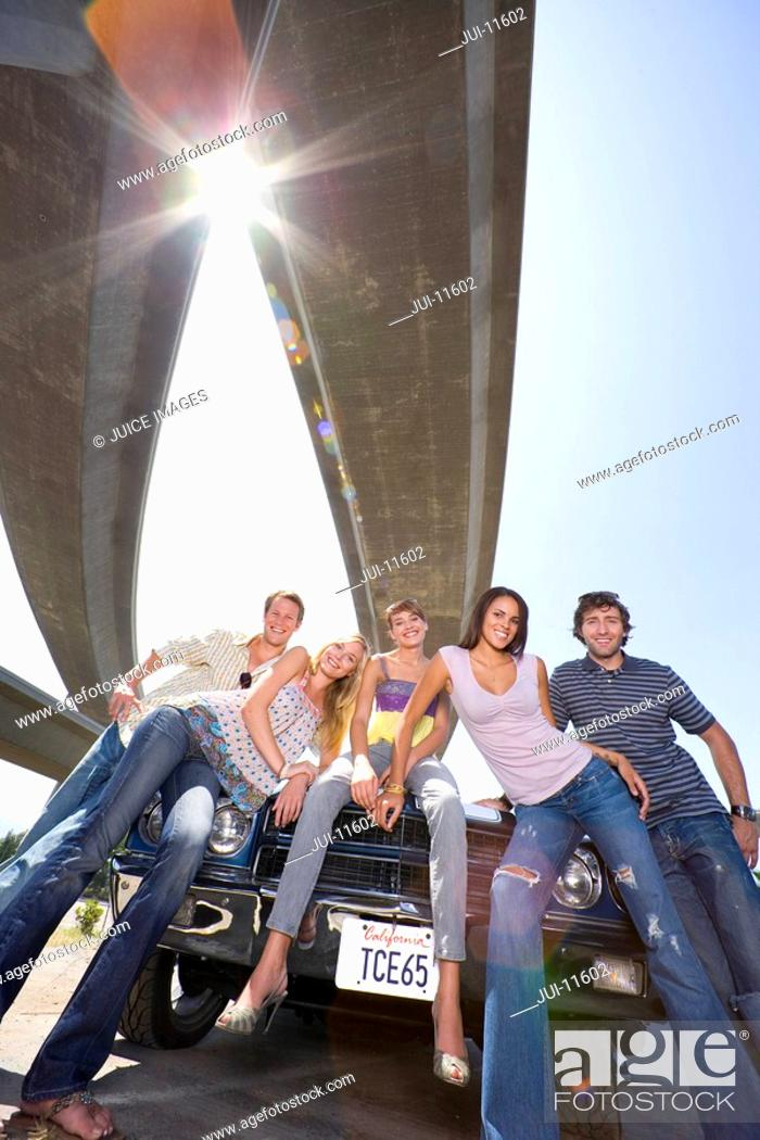 Stock Photo: Medium group of friends on bonnet of car beneath overpass, smiling, low angle view sun flare.