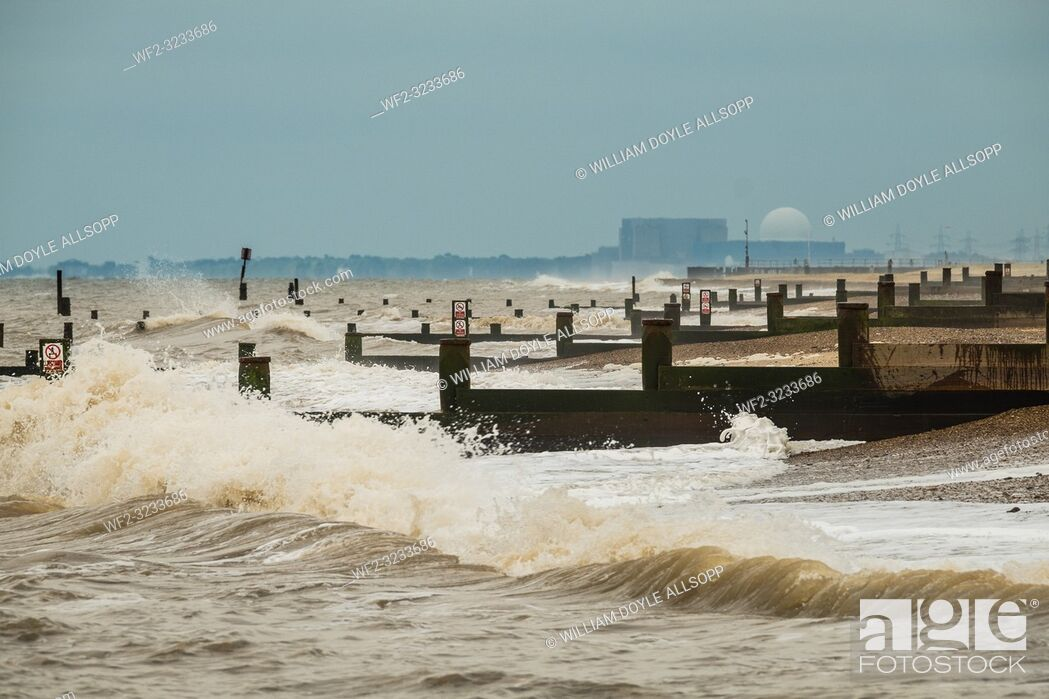 Stock Photo: Waves break on the beach and groynes at Southwold with Sizewell nuclear power station in the distance.