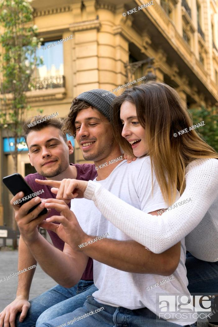 Stock Photo: Three friends using sharing cell phone in the city.