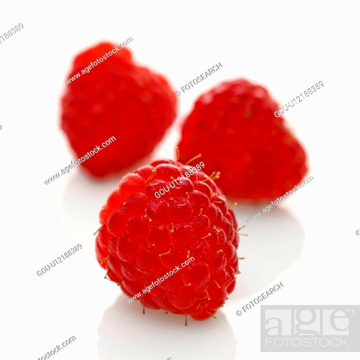 Stock Photo: Three red raspberries on white background.