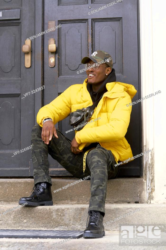 Stock Photo: stylish man sitting on stairs in front of door, Munich, Germany.