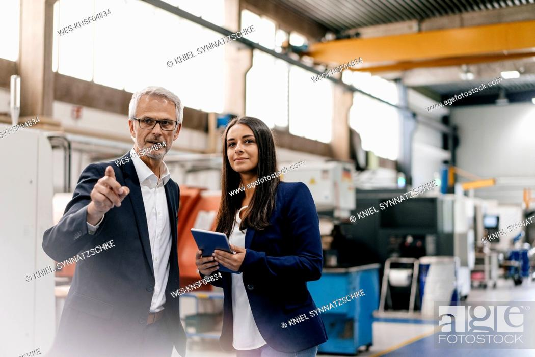 Photo de stock: Businessman an woman in high tech enterprise, having a meeting in factory workshop.