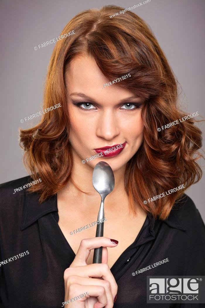 Stock Photo: Young woman holding spoon.