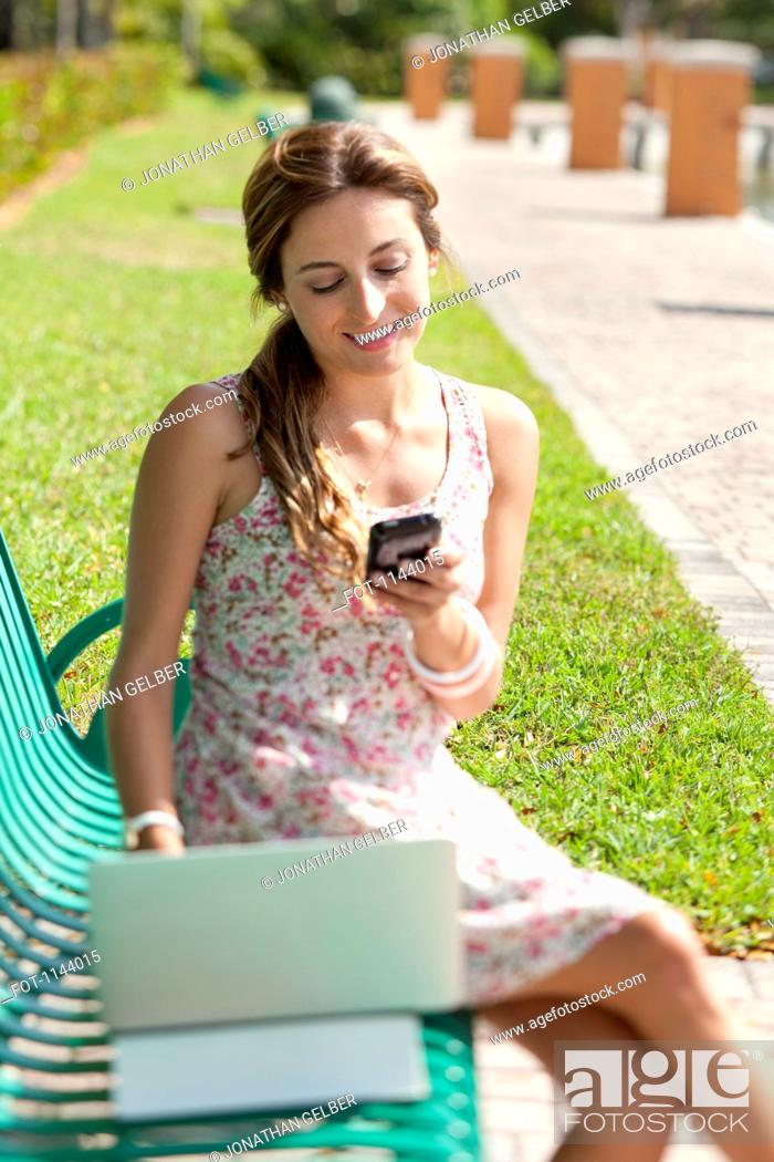 Stock Photo: A woman sitting on a park bench using a laptop and a mobile phone.