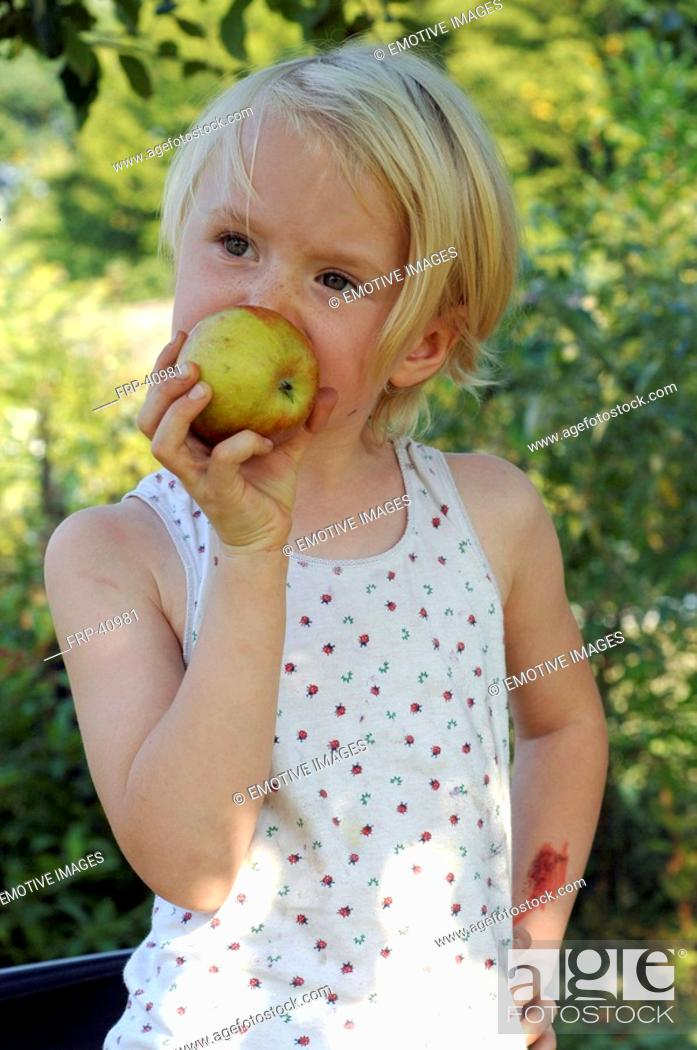 Stock Photo: Little blonde girl is biting into an apple.