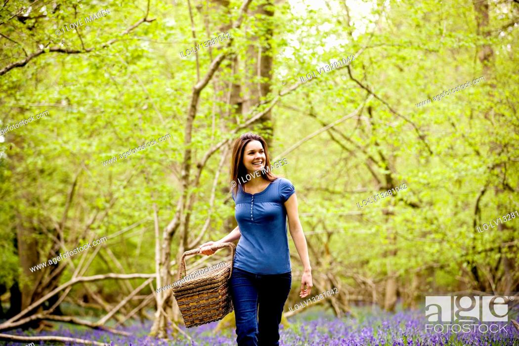 Stock Photo: A young woman walking through the woods, holding a picnic basket.