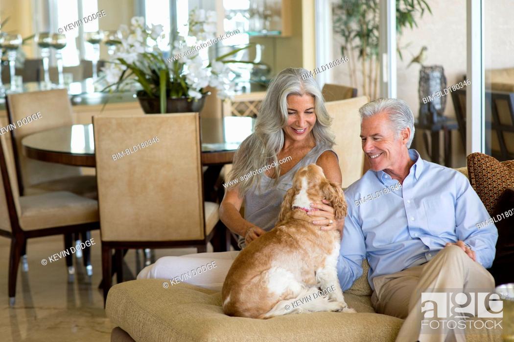 Stock Photo: Older Caucasian couple petting dog.