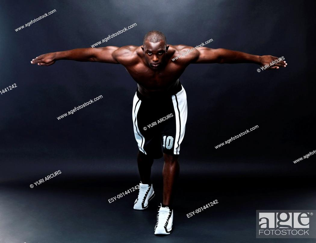 Stock Photo: Portrait of a muscular young man with his hands outstretched against grunge background.