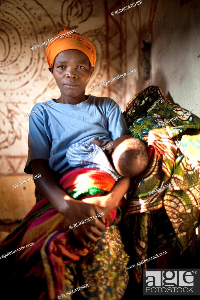 Stock Photo - woman in traditional African clothes breast-feeding her baby  in the living room of a simple mud house, Burundi, Karuzi, Buhiga