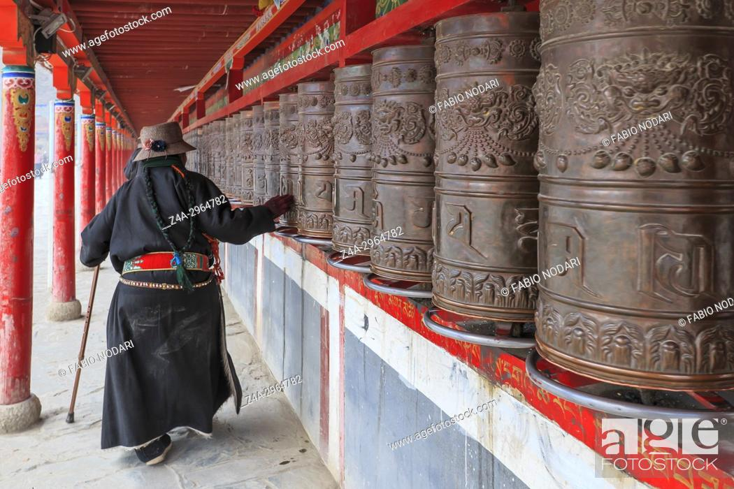 Stock Photo: Tibetan people spinning the prayer wheels around Mani Temple (Mani Shicheng) a famous landmark in the Tibetan city of Yushu (Jyekundo), Qinghai, China.