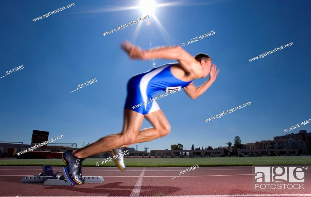 Stock Photo: Male sprinter leaving starting block, side view sun flare.