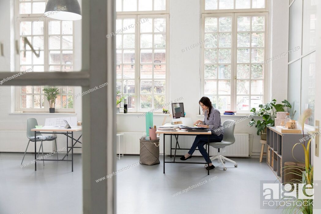 Stock Photo: Woman working at desk in a loft office.