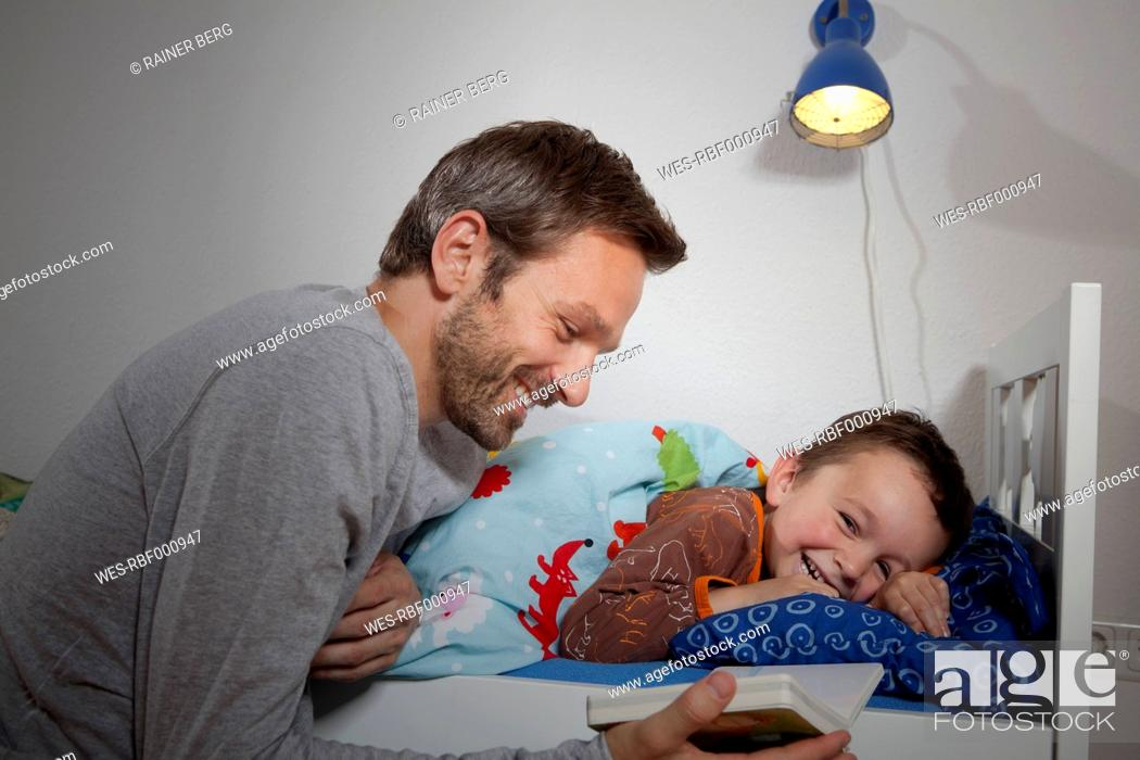 Stock Photo: Germany, Berlin, Father reading book while son sleeping.