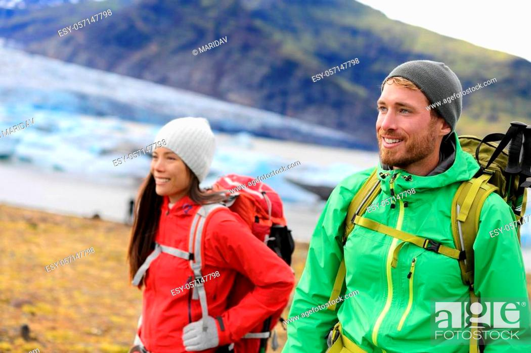 Stock Photo: Hiking adventure travel people living active healthy lifestyle wearing jackets and backpacks on Iceland by glacier and glacial lagoon / lake of Fjallsarlon.