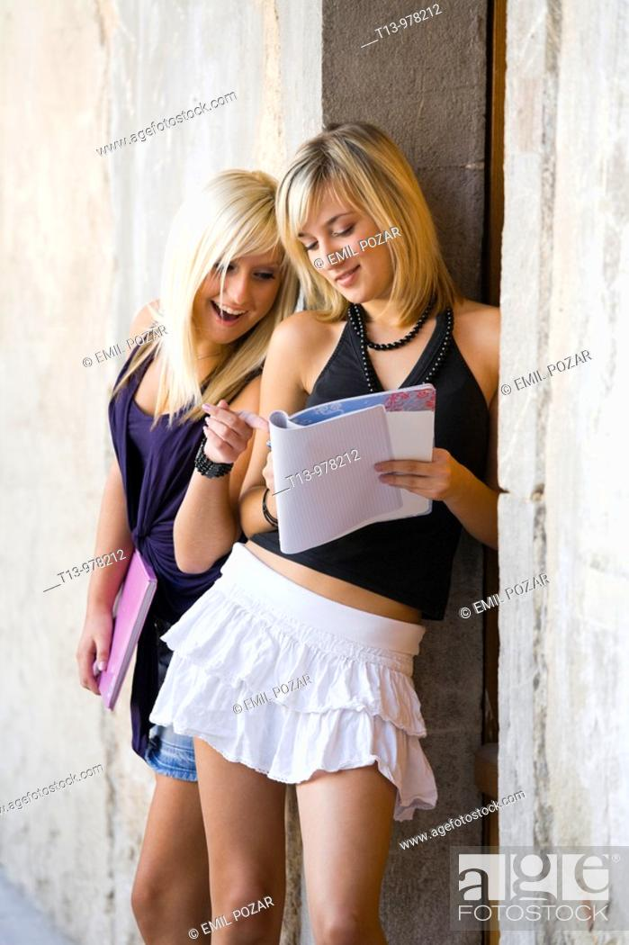 Stock Photo: Two student young women with a paper notebook, one is surprised.