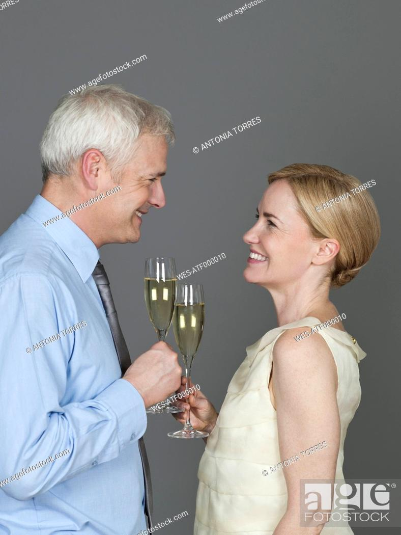 Stock Photo: Mature couple drinking sparkling wine, smiling.