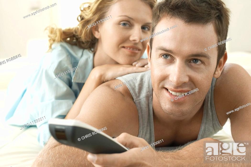 Stock Photo: Couple on bed relaxing together man holding remote control.
