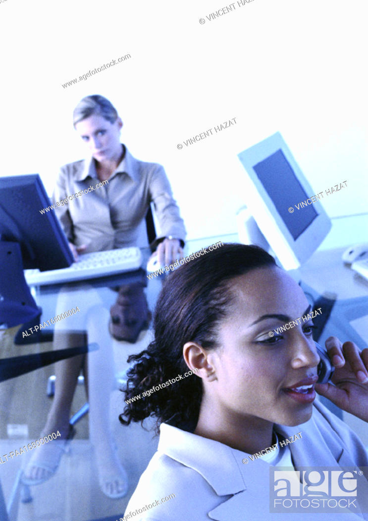 Stock Photo: Businesswomen in office, one with cell phone.