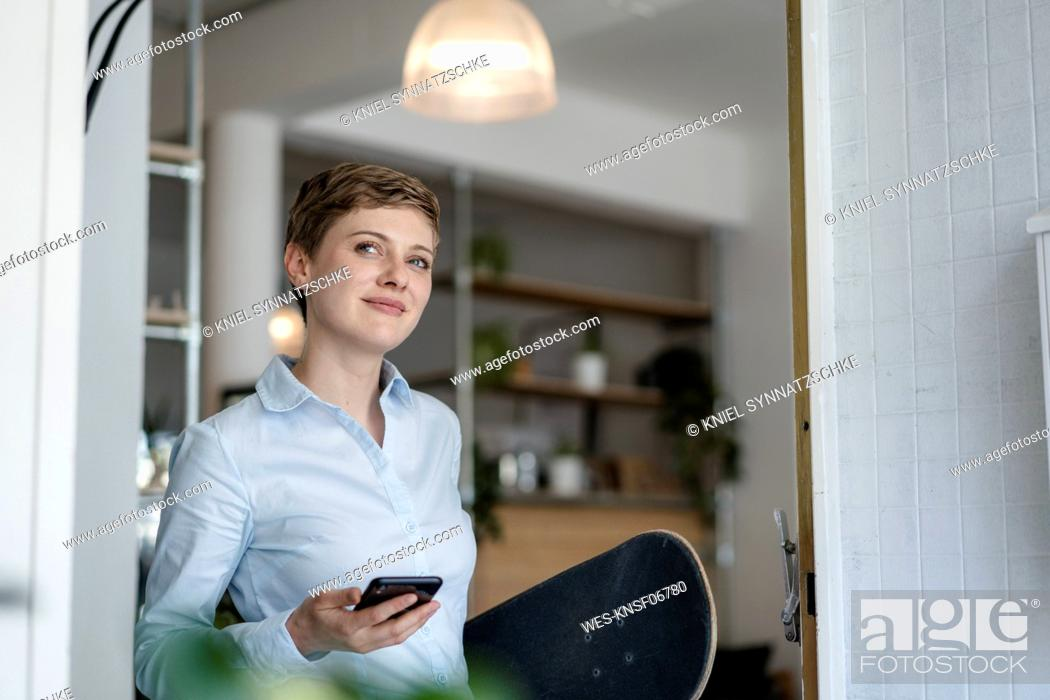Stock Photo: Businesswoman with cell phone and skateboard in a cafe.