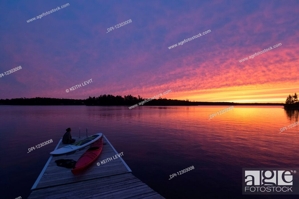 Stock Photo: A young woman sits at the end of the dock with kayaks watching the sun set over a lake; Ontario, Canada.