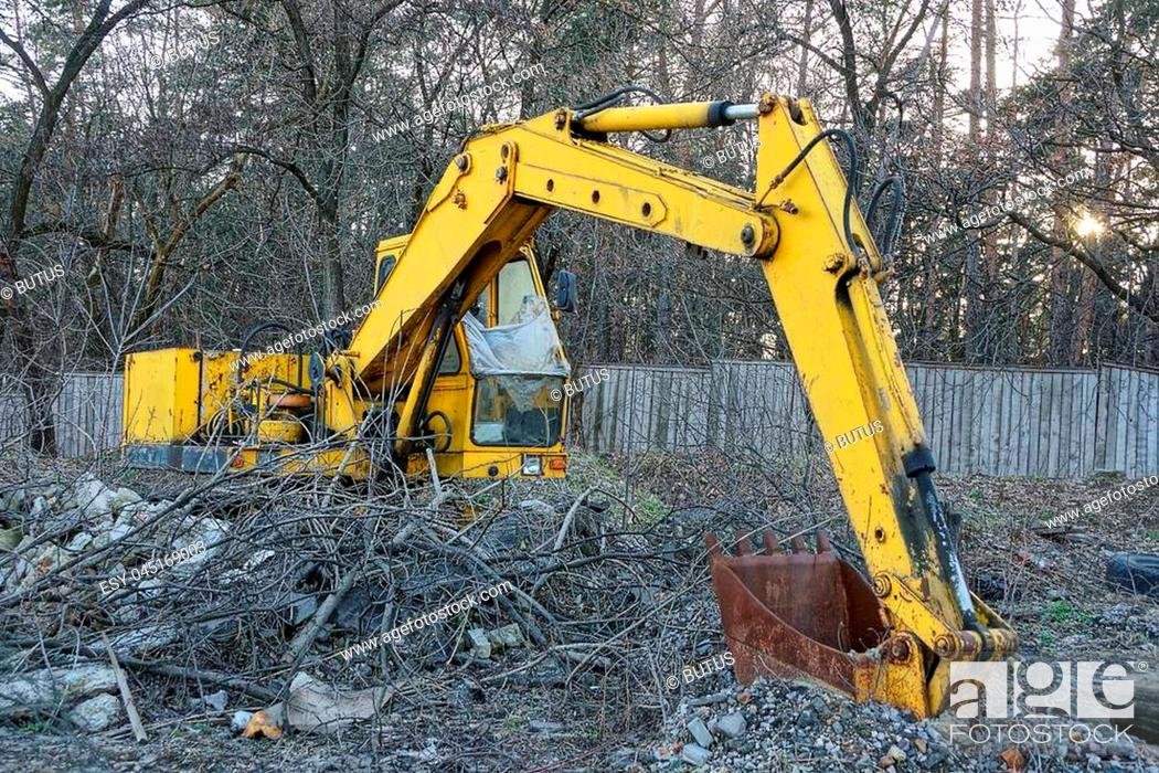 Stock Photo: old large industrial yellow excavator with a rusty bucket stands outside in the dry vegetation.