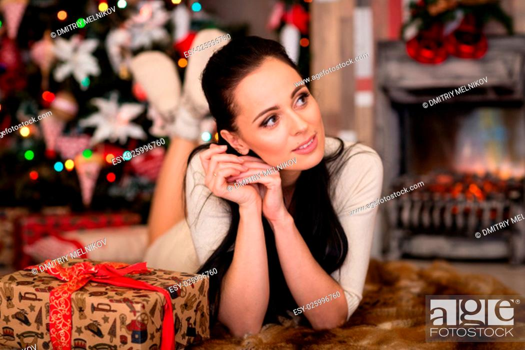Stock Photo: Young happy beautiful woman with gift box lies near Christmas tree in the room of the house. Merry Christmas and New Year.