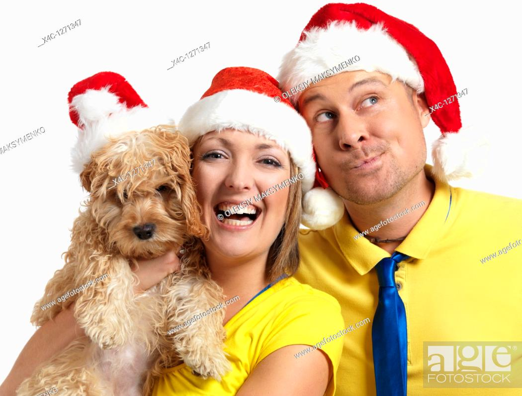 Stock Photo: Portrait of a happy young man and a woman with a Cockapoo dog in her hands wearing red Christmas hats.