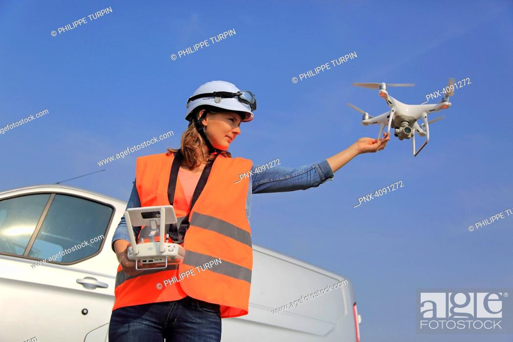 Stock Photo: Young woman using a drone.