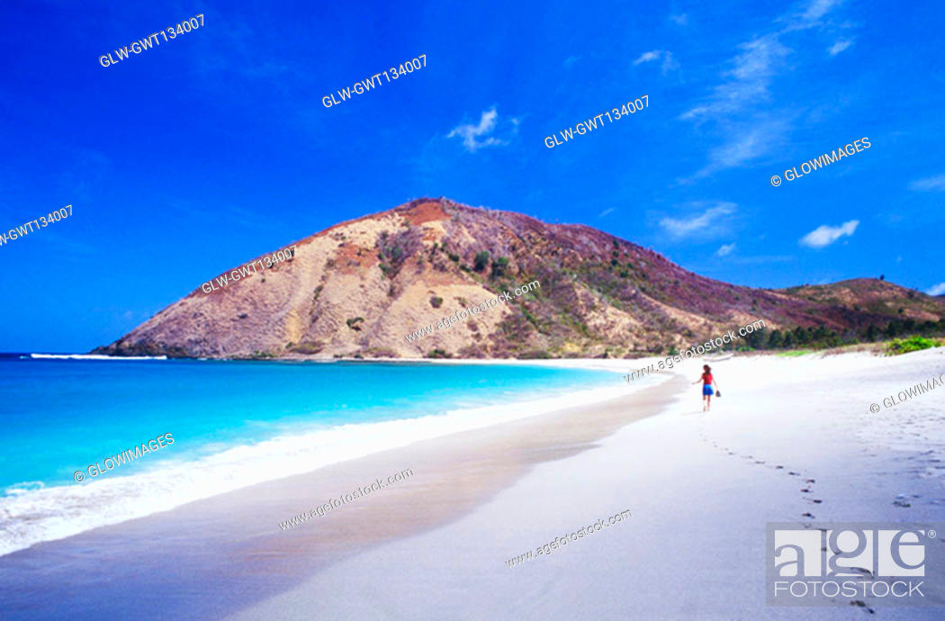 Stock Photo: Rear view of the woman walking on the beach, Bali, Indonesia.