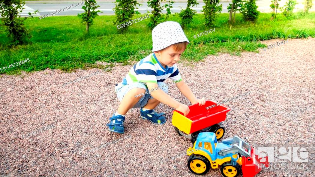 Stock Photo: Portrait of cute 3 years old toddler boy sitting on playground at park and playing with colorful plastic toy truck. Child having fun and playing outdoors with.