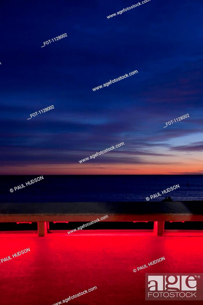 Stock Photo: View of the sea at sunset from an illuminated boardwalk.