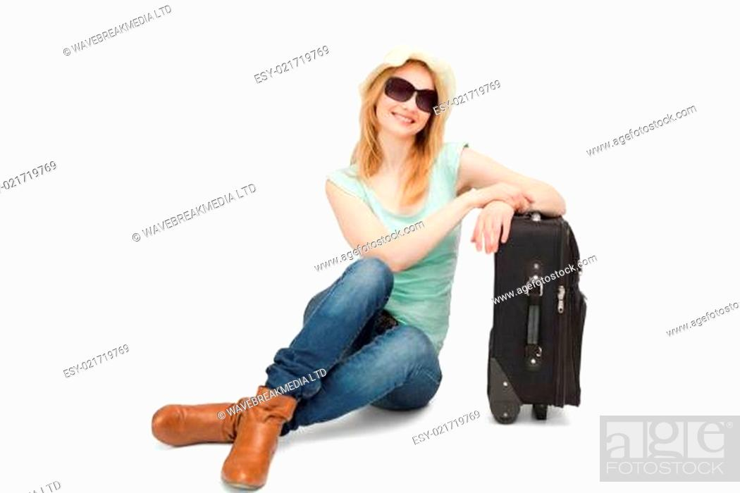Stock Photo: Woman sitting next to a suitcase.
