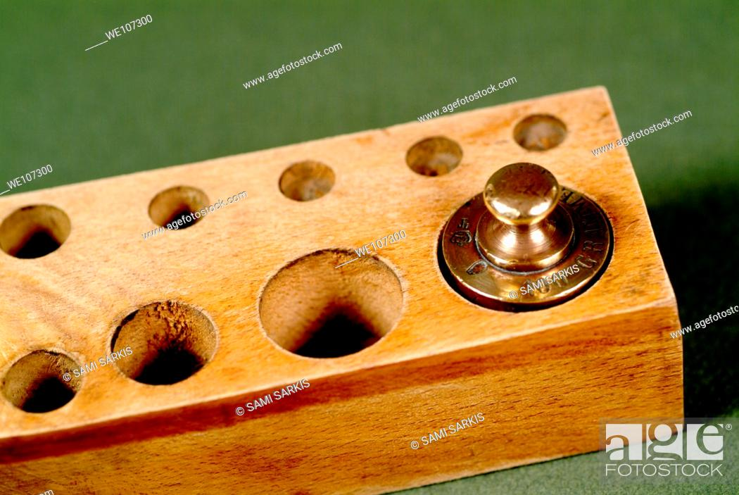 Stock Photo: Copper scale weight in a wooden box.