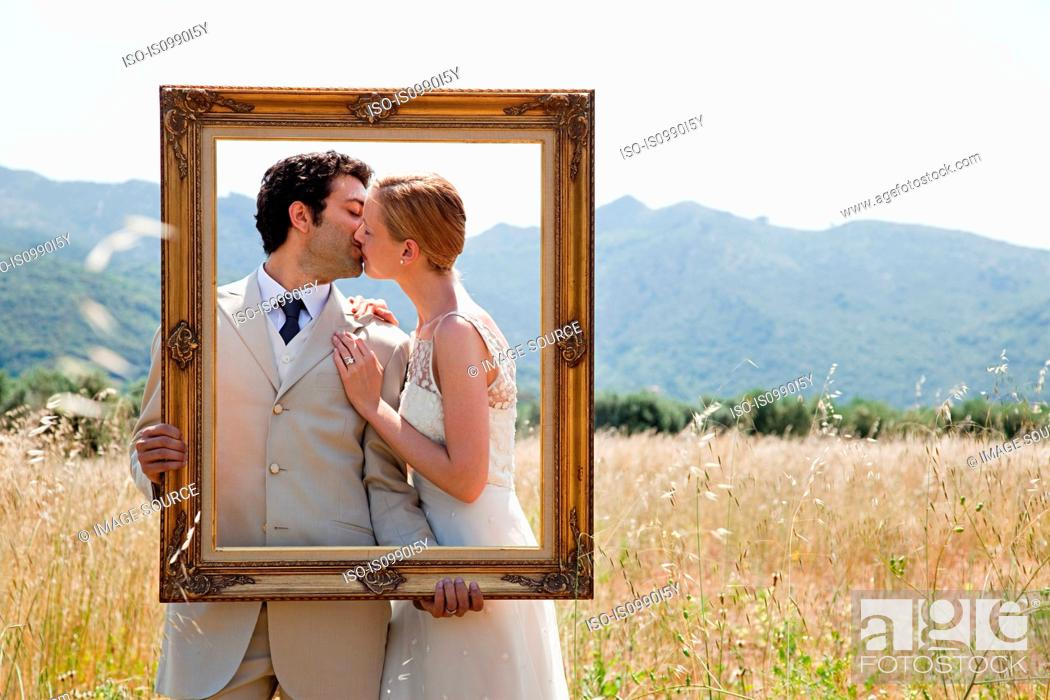 Stock Photo: Newlyweds holding vintage picture frame, kissing.
