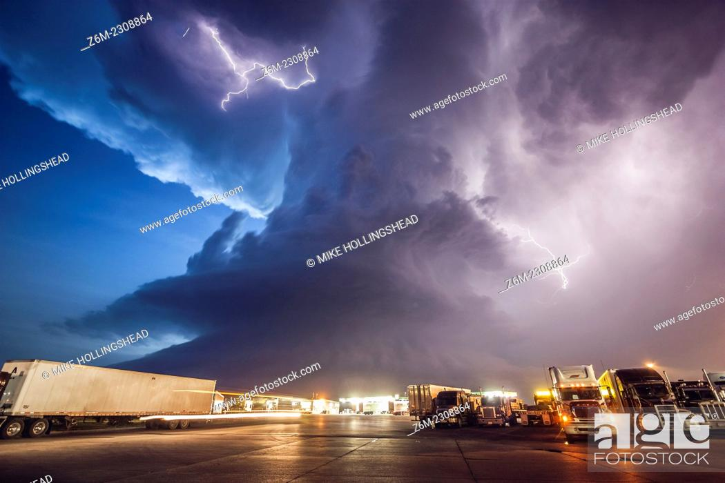 Stock Photo: Amazing supercell storm during twilight nears a York Nebraska truck stop on I80 as it spits out lightning, June 17, 2009.