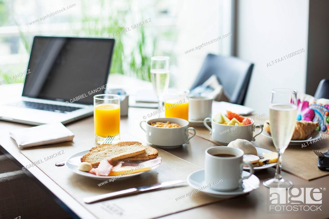 Stock Photo: Breakfast on table beside laptop computer.