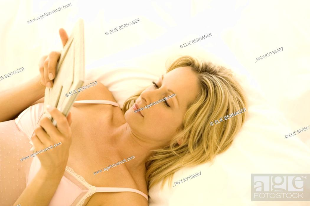 Stock Photo: Young woman lying on bed, looking at framed picture.
