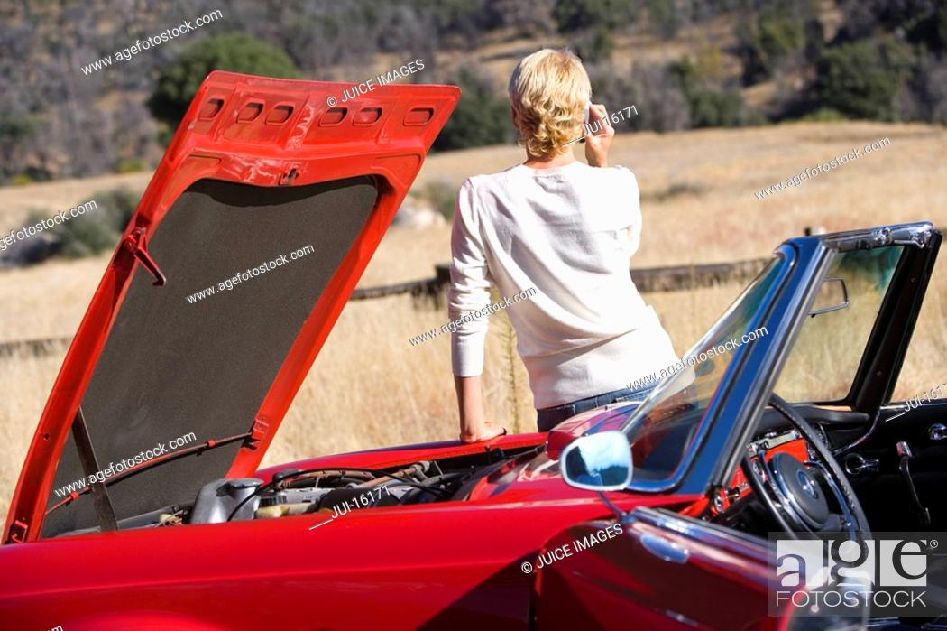 Stock Photo: Woman talking on cell phone next to broken down red convertible.