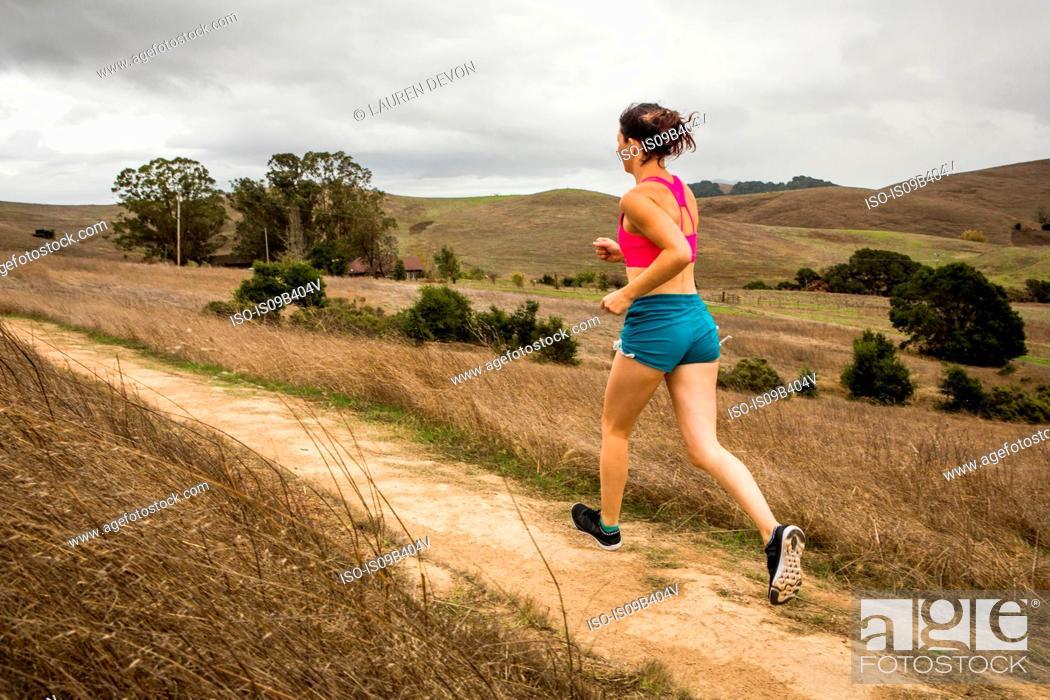 Stock Photo: Female runner running on dirt track in landscape.