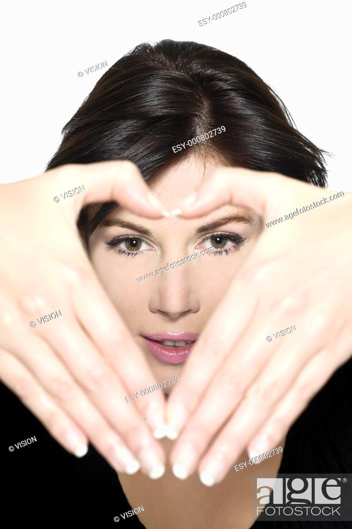 Stock Photo: studio shot portrait on isolated white background of a Beautiful Woman gesturing heart shape with hands.