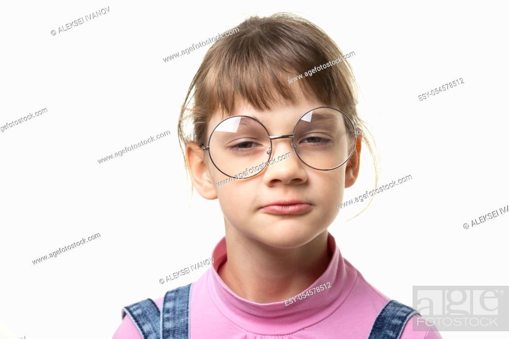 Stock Photo: Portrait of a funny girl in glasses squinting eyes on a white background.