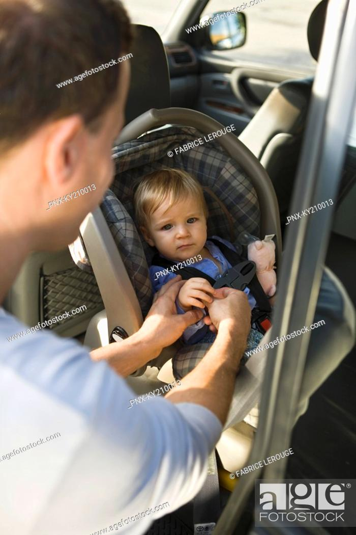 Stock Photo: Man fastening his son on a baby seat in a car.
