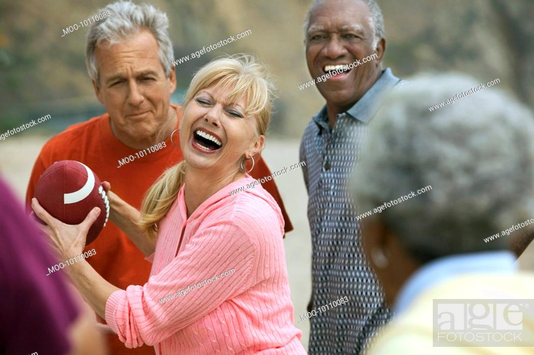 Stock Photo: Friends playing American football outdoors.