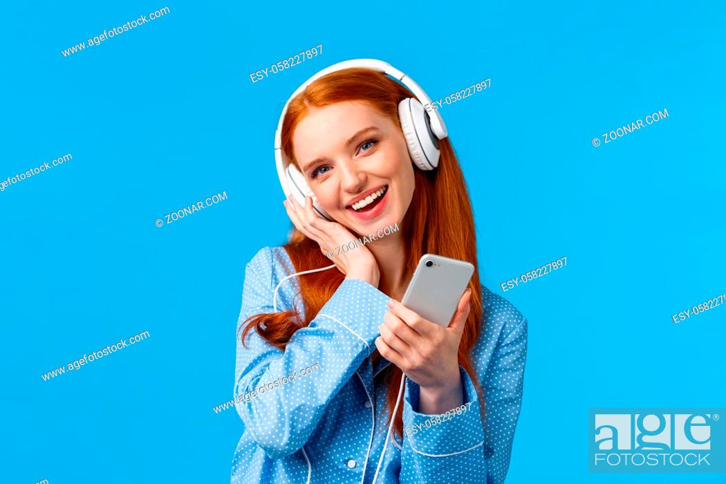 Stock Photo: Lovely young dreamy girl fantasizing as listening favorite songs, voice of singer, tilt head and touching headphone as enjoying music earphones.