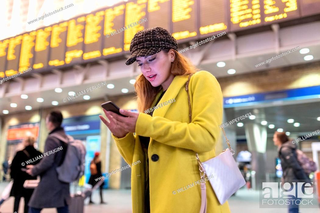 Stock Photo: Woman at train station checking her smartphone.