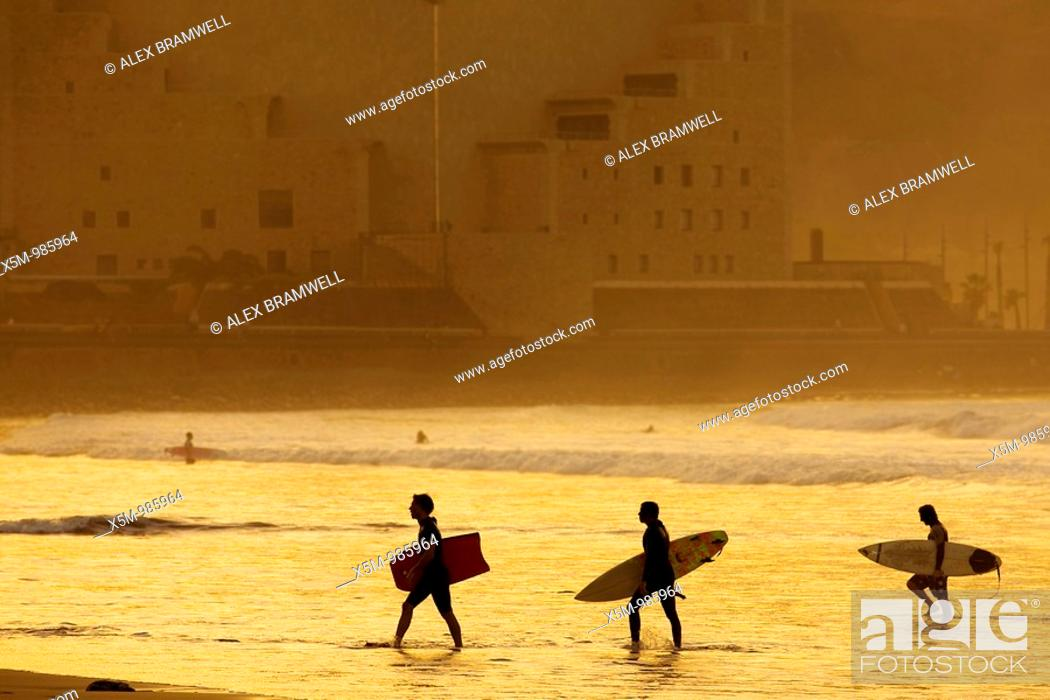 Stock Photo: Three surfers leave the water at sunset on Las Canteras Beach.